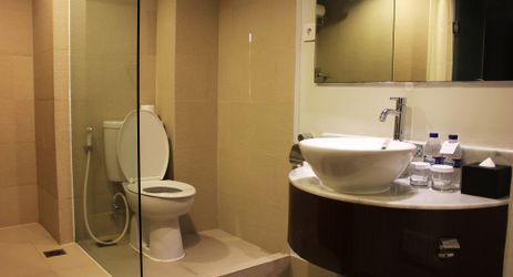 A simple en suite bathroom with rain shower and complete amenities available while staying in the commercial center of North Jakarta