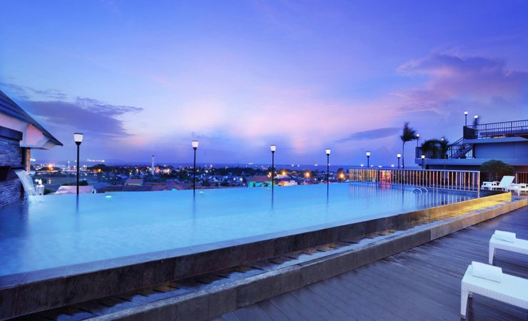 A infinity swimming pool area for children and adult to chill out and enjoy the view of Teluk Penyu sea and sunny day in Cilacap