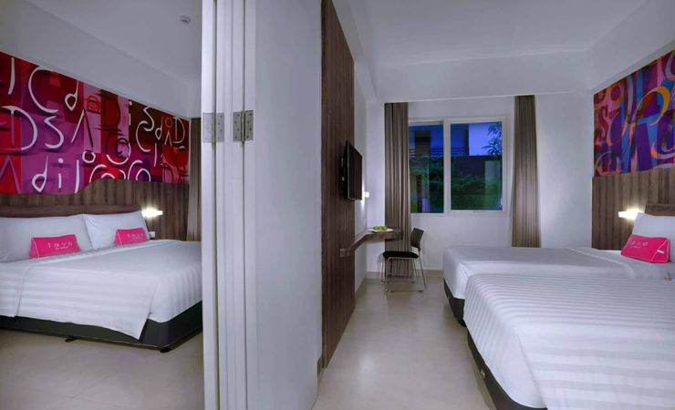 A clean and comfortable room with queen size, twin bed and connecting door of a budget hotel to stay with family while holiday in Kuta Bali