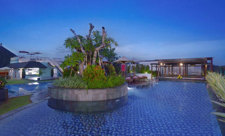 A relaxing swimming pool with kids pool in rooftop area to chill out and enjoy the clear blue sky and sunny day in Kuta Bali