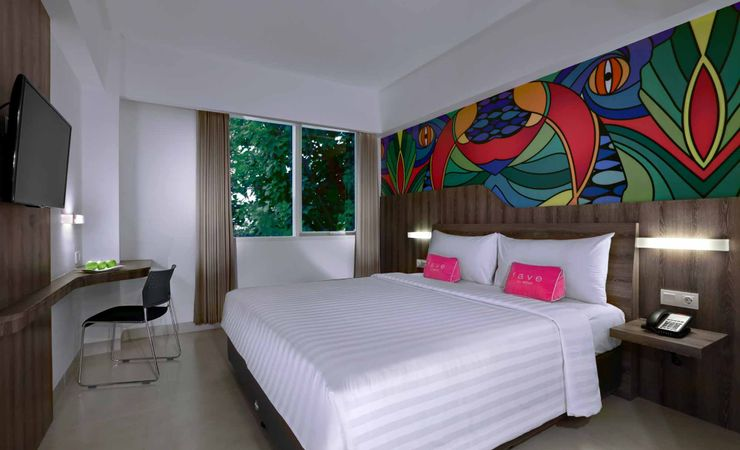 A clean and comfortable room with queen size bed of a budget hotel to stay while holiday in Kuta Bali