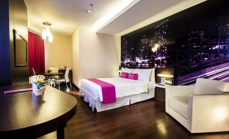 A clean and comfortable room with 52m2 suite room equipped with bathtub and standing shower of a budget hotel to stay while business trip to Surabaya