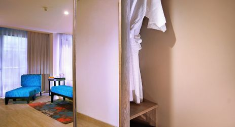 A wardrobe with bathrobes and a safe during stay in Kuta Bali
